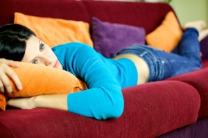 Depressed woman feeling sick at home laying on sofa