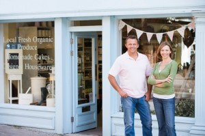 Couple standing in front of organic food store smiling