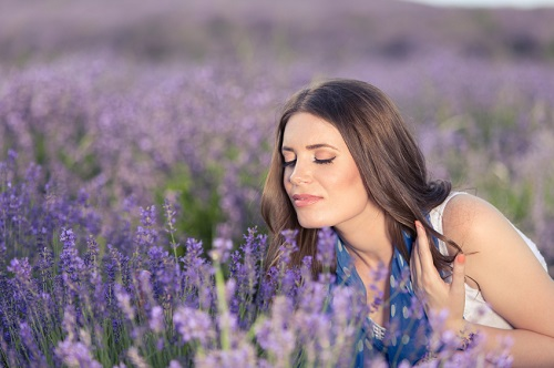Beautiful brunette enjoying the scent of lavender