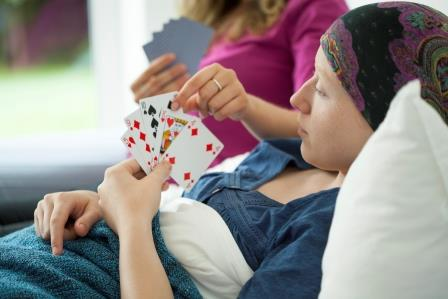 Cancer girl playing cards in hospital bed