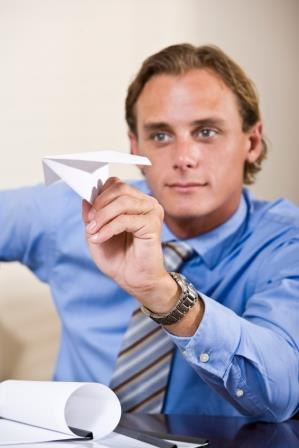 Businessman playing with paper airplane