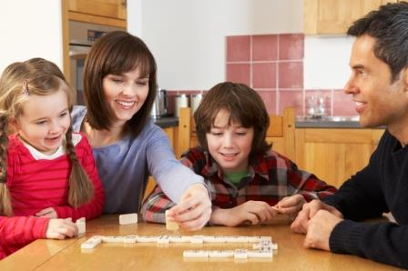 Family Playing Dominoes In Kitchen