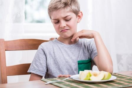 Blonde boy refusing to eat healthy apple