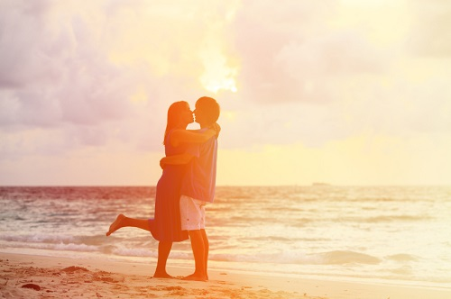 young romantic couple on the beach at sunset