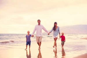 Happy Young Family Walking on the Beach at Sunset