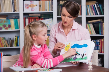 Psychologist talks with girl about a drawing