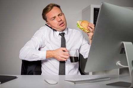 Busy man at the office having coffee and burger