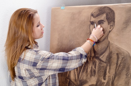 Young female artist drawing man portrait